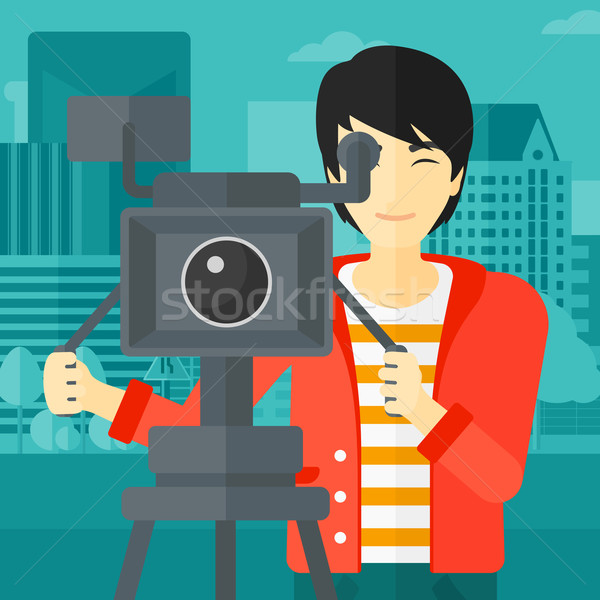 Stock photo: Cameraman with movie camera on a tripod.