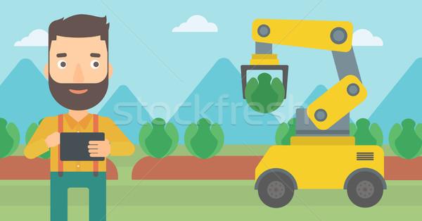 Farmer checking work of robot at the field. Stock photo © RAStudio
