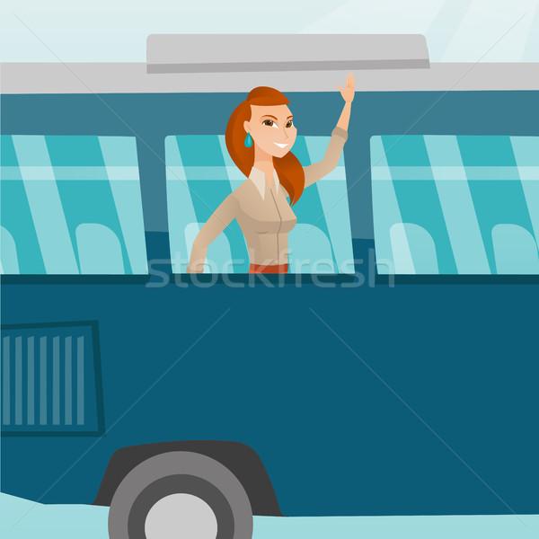 Young caucasian woman waving hand from bus window. Stock photo © RAStudio