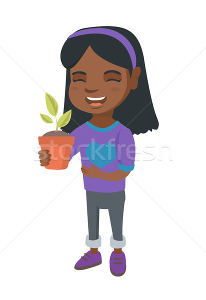 African smiling girl holding a potted plant. Stock photo © RAStudio