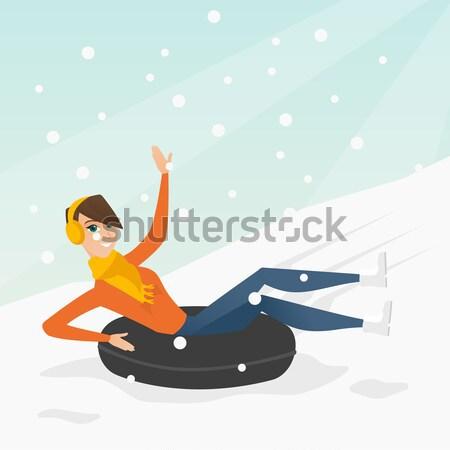 Woman sledding on snow rubber tube in mountains. Stock photo © RAStudio