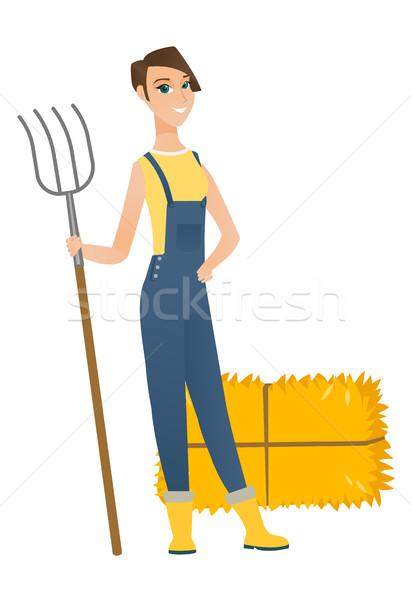 Young caucasian farmer holding a pitchfork. Stock photo © RAStudio