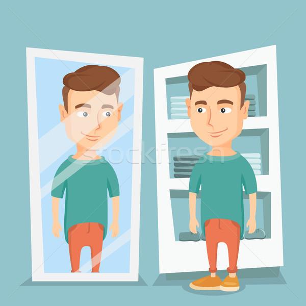 Hombre camiseta vestidor joven mirando espejo Foto stock © RAStudio