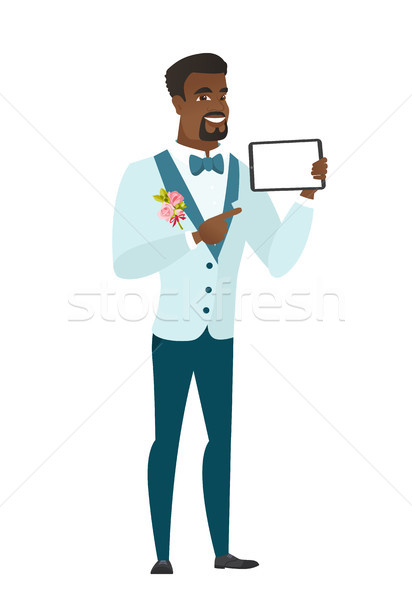 Smiling groom holding tablet computer. Stock photo © RAStudio