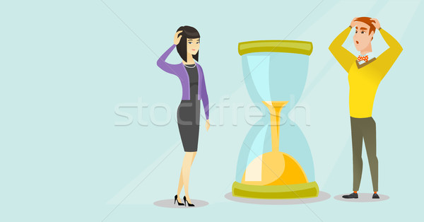 Desperate business people looking at hourglass. Stock photo © RAStudio