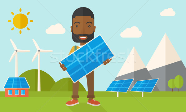 Stock photo: African man holding a solar panel.