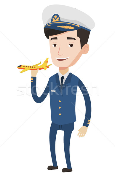 Cheerful airline pilot with model airplane. Stock photo © RAStudio