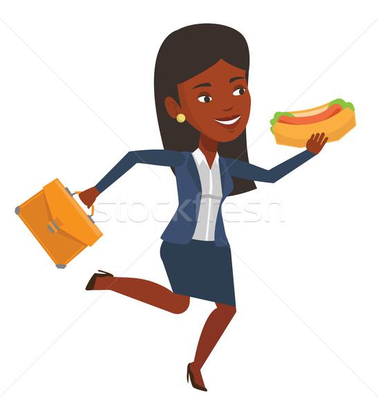 Donna d'affari mangiare hot dog fretta imprenditrice valigetta Foto d'archivio © RAStudio