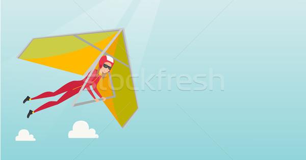 Young caucasian woman flying on hang-glider. Stock photo © RAStudio