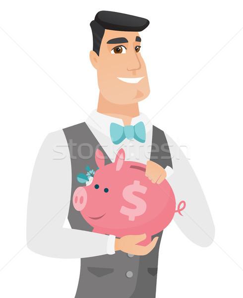 Caucasian groom holding a piggy bank. Stock photo © RAStudio