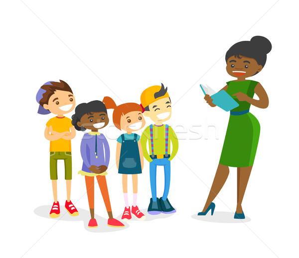 Profesor lectură carte copii tineri Imagine de stoc © RAStudio