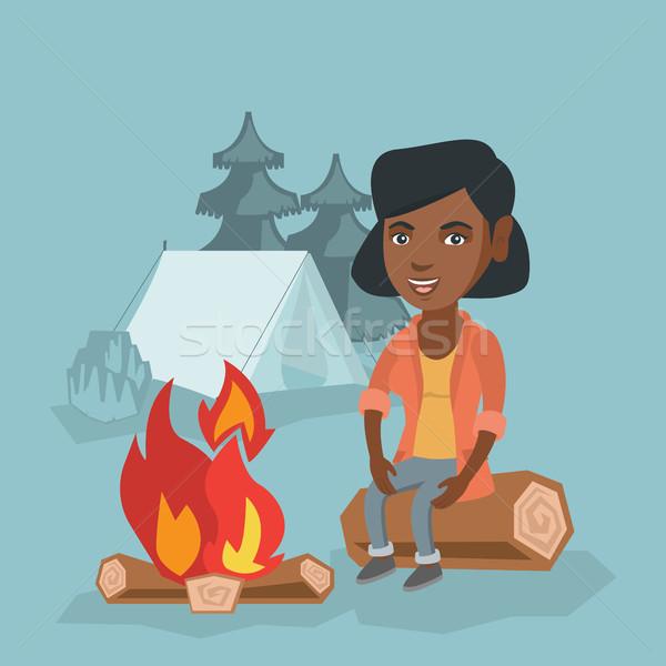 Woman sitting on log near campfire in the camping. Stock photo © RAStudio