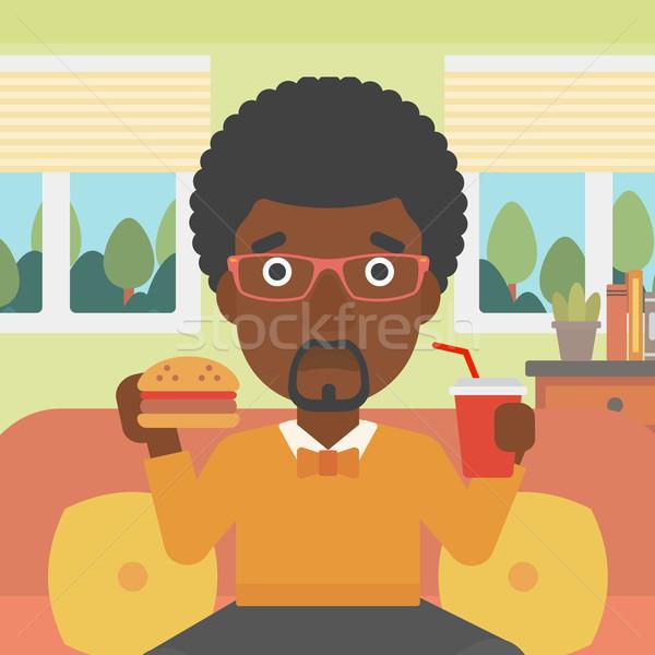 Man eating hamburger.  Stock photo © RAStudio