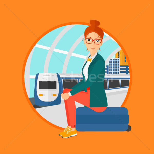 Woman sitting on suitcase at the train station. Stock photo © RAStudio
