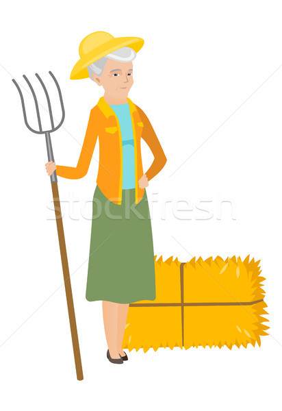 Senior caucasian farmer holding a pitchfork. Stock photo © RAStudio