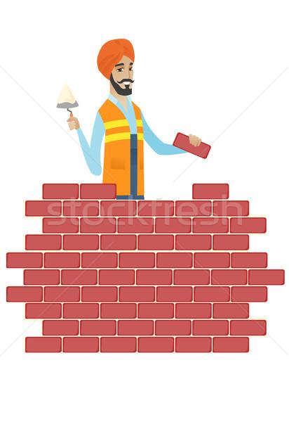 Hindu bricklayer working with spatula and brick. Stock photo © RAStudio