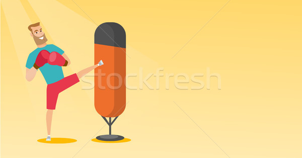 Young caucasian man exercising with punching bag. Stock photo © RAStudio