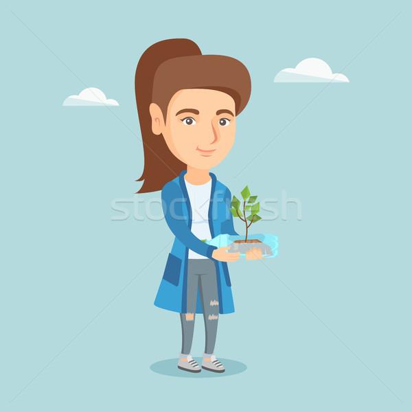 Woman holding plant growing in a plastic bottle. Stock photo © RAStudio