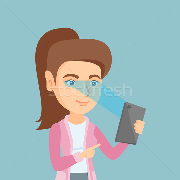 Woman using iris scanner to unlock a mobile phone. Stock photo © RAStudio