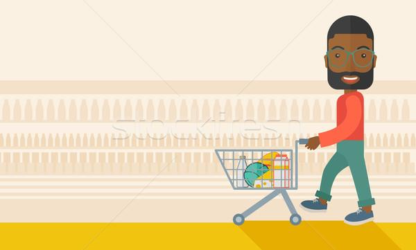 Black Male Shopper Pushing a Shopping Cart. Stock photo © RAStudio