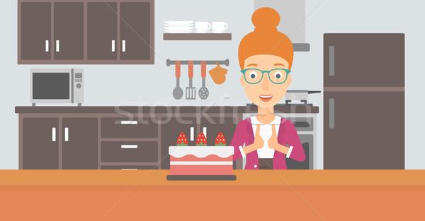 женщину глядя торт счастливым Постоянный кухне Сток-фото © RAStudio