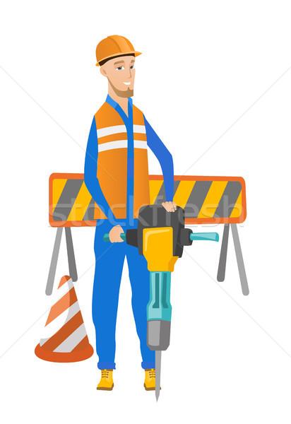Young caucasian builder using pneumatic hammer. Stock photo © RAStudio