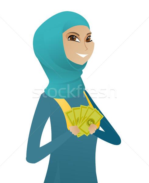 Young muslim business woman holding money. Stock photo © RAStudio