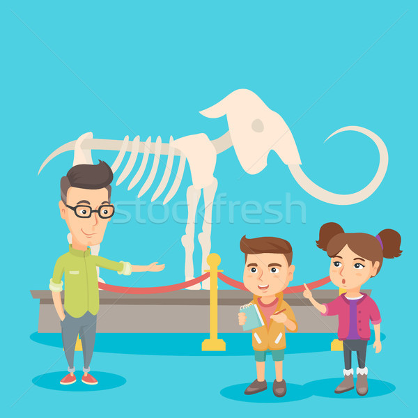 Kids with a teacher studying a skeleton in museum. Stock photo © RAStudio