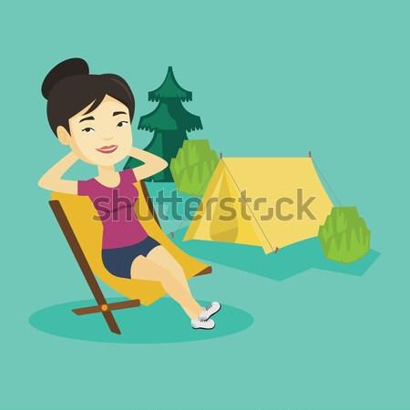 Woman sitting in folding chair in the camp. Stock photo © RAStudio