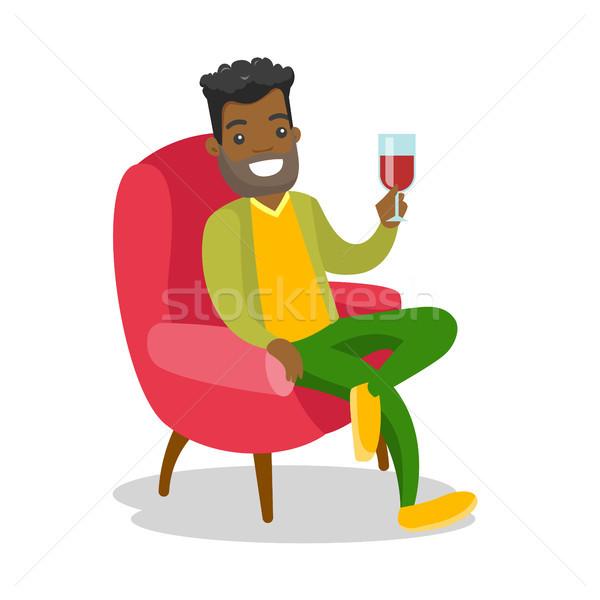 African-american man drinking wine in the chair. Stock photo © RAStudio