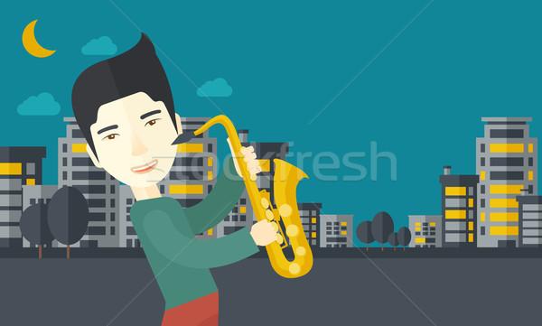 ázsiai zenész játszik szaxofon utcák éjszaka Stock fotó © RAStudio