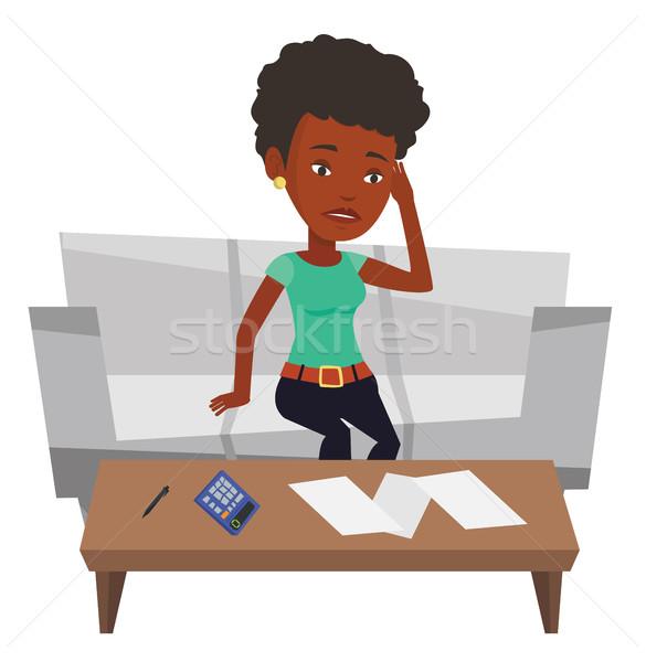 Unhappy african woman accounting home bills. Stock photo © RAStudio