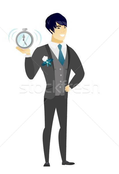 Asian groom holding alarm clock. Stock photo © RAStudio
