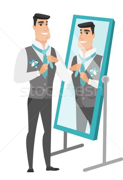 Groom looking in the mirror and adjusting tie. Stock photo © RAStudio