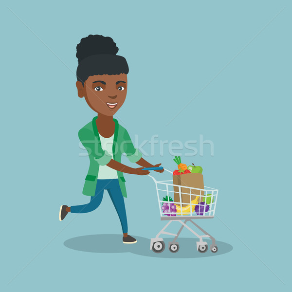 African woman running with a shopping cart. Stock photo © RAStudio
