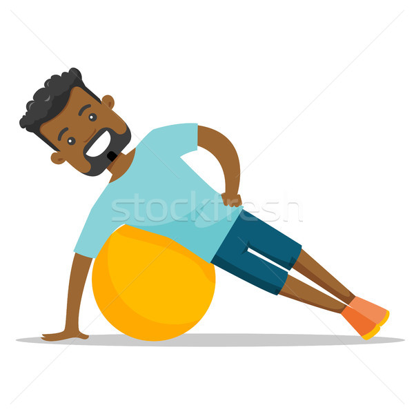 Young african-american man exercising with fitball Stock photo © RAStudio
