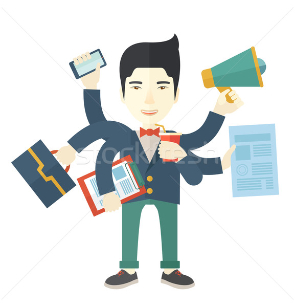 Young but happy japanese employee doing multitasking office tasks. Stock photo © RAStudio