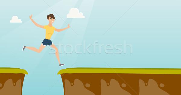 Young caucasian sportswoman jumping over the cliff Stock photo © RAStudio