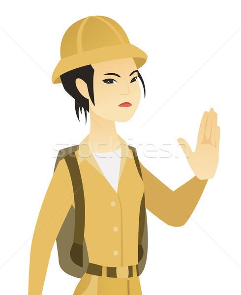 Young asian traveler showing stop hand gesture. Stock photo © RAStudio