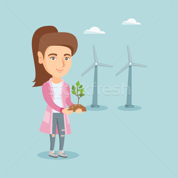 Caucasian worker of wind farm holding small plant. Stock photo © RAStudio
