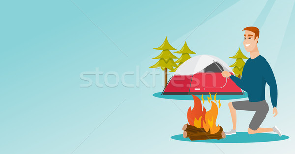 Young caucasian white man making the campfire. Stock photo © RAStudio