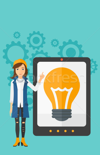 Woman pointing at tablet computer with light bulb on screen. Stock photo © RAStudio