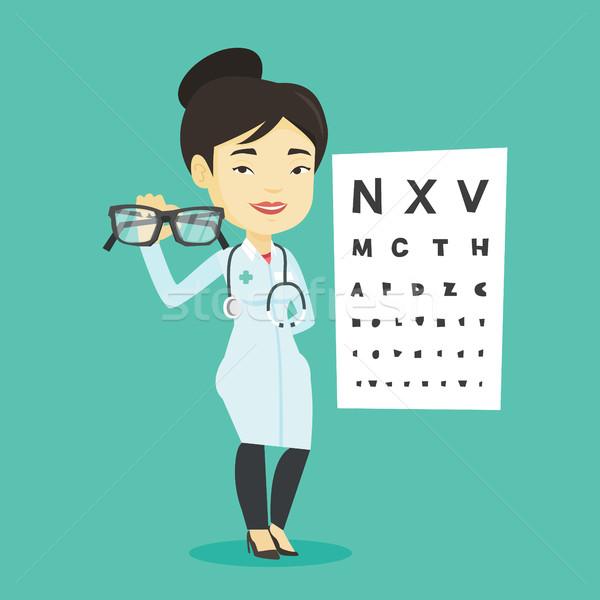 Professional ophthalmologist holding eyeglasses. Stock photo © RAStudio