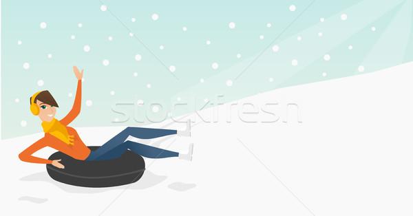 Girl sledding on snow rubber tube in the mountains Stock photo © RAStudio