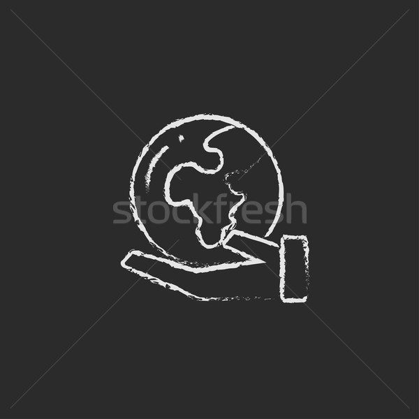 Hand holding the Earth icon drawn in chalk. Stock photo © RAStudio