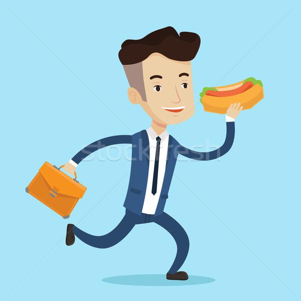 Işadamı yeme sosisli sandviç gülen acele mutlu Stok fotoğraf © RAStudio