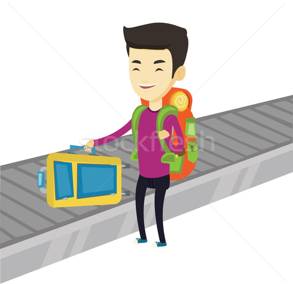 Man picking up suitcase on luggage conveyor belt Stock photo © RAStudio
