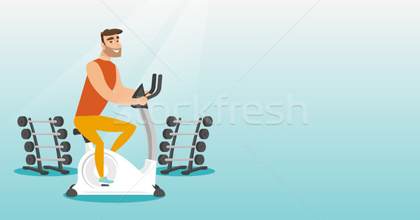 Young man riding stationary bicycle. Stock photo © RAStudio