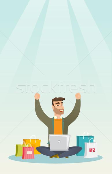 Caucasian man using a laptop for online shopping. Stock photo © RAStudio