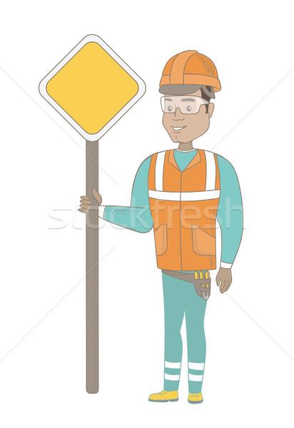 Young hispanic road worker showing road sign. Stock photo © RAStudio